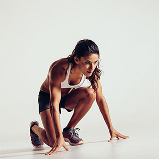 A runner getting into position to begin a race.
