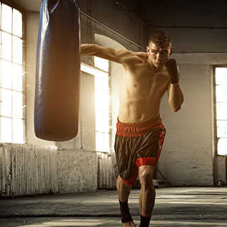 Striking a punching bag in a gym.